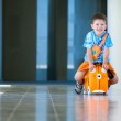 Cute happy boy with a suitcase at airport — Stock Photo #11011768