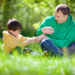 Stock Photo: Happy father playing with his little son outdoors