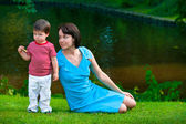 Cute two years old boy with his young mom in park — Stock Photo