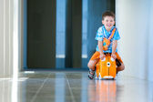 Cute happy boy with a suitcase at airport — Stock Photo