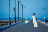 Happy woman and her little son on wooden jetty — Stock Photo