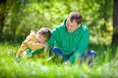 Cute little boy hugs his father outdoors — Stok fotoğraf