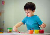 Cute toddler boy painting with brush — Stock Photo