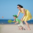 Young mother and son playing on the beach — Stock Photo #11167384