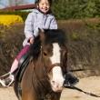 Preschool girl ride on pony — Stock Photo