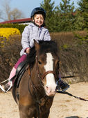 Preschool girl ride on pony — Stock Photo