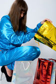 Girl in blue clothes looks in a golden package — Stock Photo