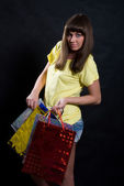Girl with multi-colored packages — Stock Photo
