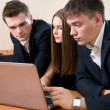 Three young businessmen with laptop — Stock Photo
