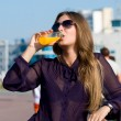 Stock Photo: Girl in dark glasses drinks orange drink