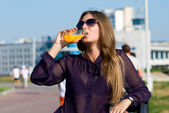 Girl in dark glasses drinks orange drink — Stock Photo