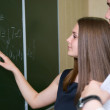 The young student shows a hand on a board - Foto Stock