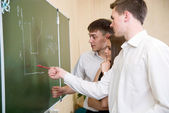 Students at a board solve a problem — Stock Photo