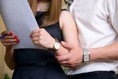 Kobieta trzyma dokument i człowiek w pobliżu trzyma ją za rękę — Zdjęcie stockowe