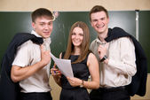 Three young succeeding the businessman against a board — Stock Photo
