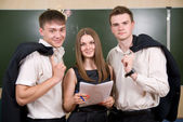 Three young succeeding businessman against a board — Stock Photo