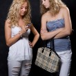 Two blondes look in the cell phone — Stock Photo