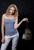 Beautiful blonde with a bag on a finger — Stock Photo