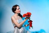Mujer embarazada tiene flores rojas en las manos estiradas — Foto de Stock