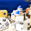 Santorini traditional blue and white village and church in Oia and sea view , Greece — Stock Photo #11926554