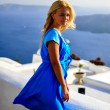 Stock Photo: Young vacationing beautiful happy girl in blue dress In Santorini