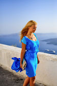 Young vacationing beautiful happy girl in blue dress flying in Santorini — Stock Photo
