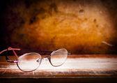 Gamla glasögon på skrivbord — Stockfoto
