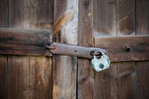 Old wooden doors with green padlock — Stock Photo