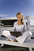 Young woman with a laptop on the pier — Stock Photo