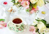 Flowers and cup of tea — Stock Photo
