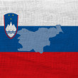Flag and map of Slovenia  on a sackcloth — Stock Photo