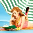 Stock Photo: Beautiful sexy girl pin up in a pink bikini reads book on the beach under sun umbrella