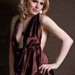 Pretty confident blonde girl in evening dress, posing against a — Stock Photo