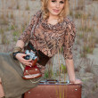 Stock Photo: Girl travels in cowboy hat, with camerand suitcase in