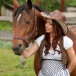 A beautiful  girl in a cowboy hat with a horse - Stock Photo