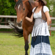 A beautiful  girl in a cowboy hat with a horse — Stock Photo