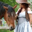 Beautiful girl in cowboy hat stroking horse — Stock Photo #12003368