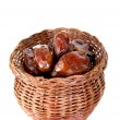 Dates in bamboo jar on white background — Stock Photo