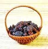 Black raisin in wicker basket on matting sunlight background — Stock Photo