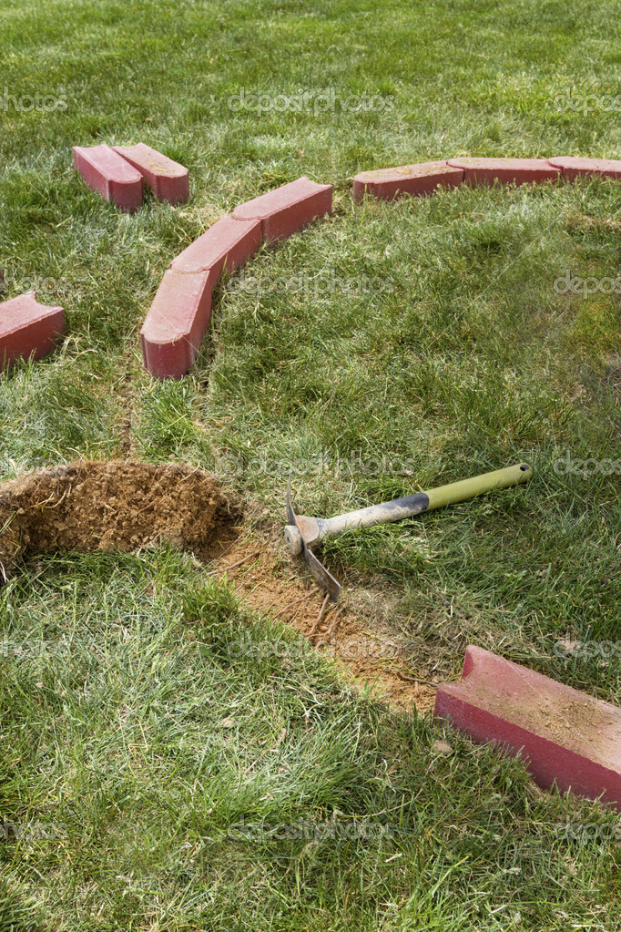 Installing brick edging with one side rounded bricks by removing the grass. — Stock Photo #11046881