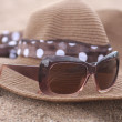 Brown summer hat and goggles on the Sand - Foto Stock