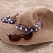 Straw hat and sunglasses on a beach — Stockfoto