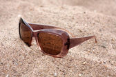 Sun glasses on a sand — Stock Photo