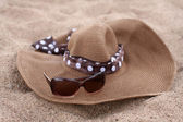Straw hat and sunglasses on a beach — Stock Photo