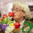 Grandmother with flowers on a blurry room background — Stock Photo