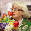 Stock Photo: Grandmother with flowers on blurry room background