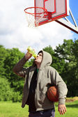 Man holding basketball and drink from bottle of water — Zdjęcie stockowe