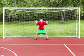 Boy standing in football goal — Stock Photo