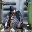 Stock Photo: Tramp sleeping near dumpsters