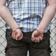 Man in handcuffs behind wire fence — Stock Photo